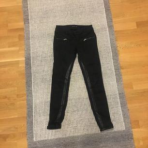 Svarta jeans från Stradivarius med skinndetaljer på benen och dragkedjor vid fickorna. Normal midjehöjd. Storlek 36. Säljer för att de är för små. Kan skicka eller mötas upp i Stockholm! Köpare står för frakt.
