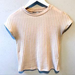 Ljusrosa T-shirt i kortare modell i storlek XS från Monki säljes för 20kr, frakt tillkommer. Betalning sker via swish.