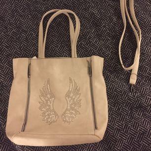 Fin vit/beige väska. Den är rymlig och i jättebra skick. Man kan även sätta på ett längre band som ni ser till höger om väskan på bilden.