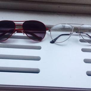 Två par jättesnygga glasögon, den röda är solglasögon med bågar i metall, och den andra är glasögon färgen är silver i pilotmodell med metallbågar. Klarglas.