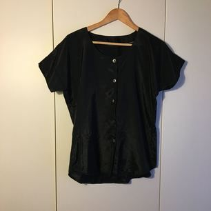 True vintage black satin shirt with natural buttons. Interesting shape arms and flattering cut.