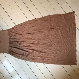 En ljusrosa långkjol som en också kan ha som klänning. S i bysten men M vid nederdelen och är i runt tyg. Jag har använt den ganska mycket och är några år gammal.