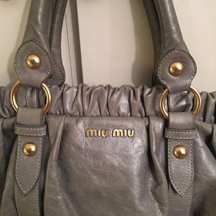 Miu miu väska i blågrå färg. Köptes begagnat för 5500 kr. Säljer den oerhört billigt för att väskan inte används. Har ett hål i innerfickan men ingenting som man märker av. Vid intresse kan jag ta fler bilder. Möts i sthlm,huddinge.
