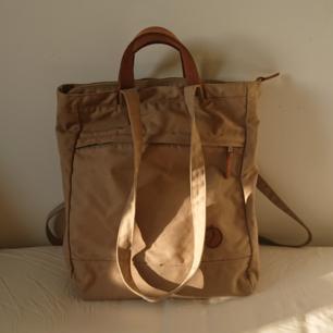 Säljer denna Fjällräven väska, modell Totepack No. 1 I färgen Sand då den alltför ofta blir bortprioriterad av min kånken. Väldigt rymlig och den bakre remmen går och justera så man kan bära den både som axelväska och som ryggsäck. Köparen betalar frakt, men kan mötas upp i Stockholm!
