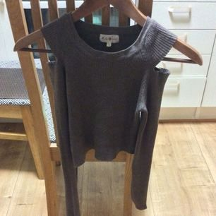En midjekort brun tröja med hål/ bart om axlarna, sitter jätte snyggt på och är i storlek XS/S.