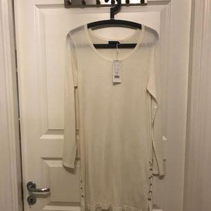 Helt ny klänning med taggen fortfarande kvar