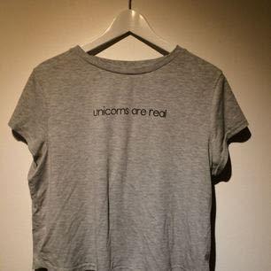"""Grå lite croppad t-shirt från H&M med trycket """"unicorns are real"""". Den är i väldigt bra skick.   Fraktar ej men kan mötas upp i Sthlm"""