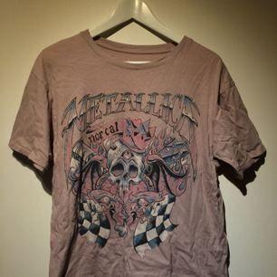 Ljusrosa t-shirt från pull & bear med snyggt Metallica tryck. Den är i bra skick och lite baggy i modellen, står M på lappen men skulle säga att den även passar L beroende på vilken passform en söker.  Fraktar ej men kan mötas upp i Sthlm.