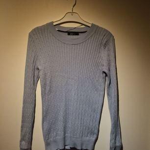 Klassisk ljusblå kabelstickad tröja från Gina Tricot i bra skick.   Fraktar ej men kan mötas i Sthlm.