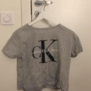 """Grå Calvin Klein tröja i den """"croppade"""" modellen. Använd ett par gånger men har ingen defekt!"""