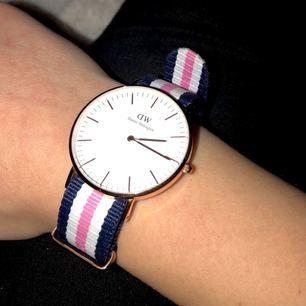 Äkta klocka från Daniel Wellington i roséguld, använd men i bra skick. Vit/rosa/marinblått band.  Obs!! Inget batteri. Köparen står för frakt