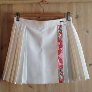 """Vintage tenniskjol från Adidas från 80-talet, tjockt tyg som får fin siluett. Spännes med en slags """"dragkedja"""" plus kardborrband, så är ganska flexibel i storleken. Den är lite kortare i modellen då det är en sport-kjol."""