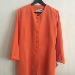 Matt korallfärgad/orange kavaj med klädda knappar. Strl. 40 men passar även perfekt på mig som brukar ha 36-38.  Upphämtas i Göteborg eller skickas. Köparen står för frakten!