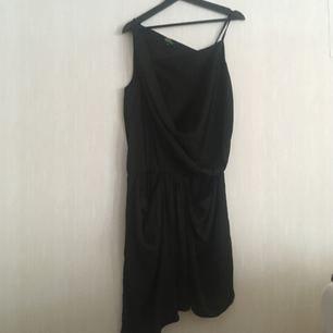Svart asymmetrisk klänning med resor i midjan och sidofickor. Knappt använd!  Kan hämtas i Göteborg eller skickas. Köparen står för frakten!