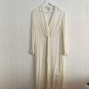 Vacker lång skjorta i benvitt med djup v-ringning och knytbara detaljer på framsidan.  Kan upphämtas i Göteborg eller skickas. Köparen står för frakten!