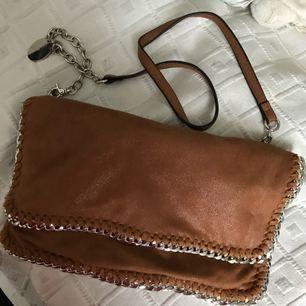 En jättefin oanvänd Stella McCartney inspirerad väska/clutch. Går att ta av axelbandet så blir det en jättefin clutch till våren!