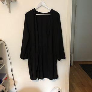 En svart lång kofta i tunt material från Ginatricot, perfekt till att styla upp andra plagg med. Är i väldigt fint skick! Storlek 40