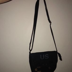 En svart praktisk liten väska med ett innerfack (se bild 3) Saknas en rem