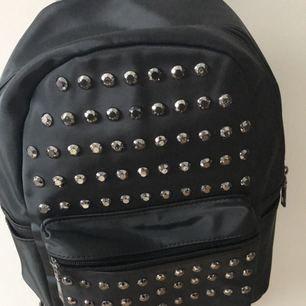 En svart lite mindre  ryggsäck med nitar på, näst intill oanvänd