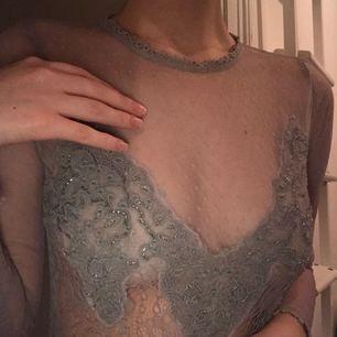 Lite genomskinlig topp med dekorativa saker för brösten, funkar med att ha bh eller något liknande under!