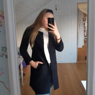 En fin marinblå kappa i storlek 38, armarna är lite korta för mig som är 174 och har storlek 38 i vanliga fall.