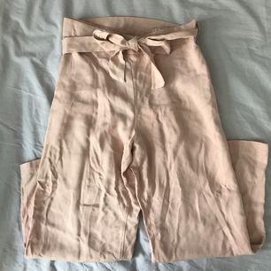 Ljusrosa vida byxor med knyte i midjan, kan användas som både vanliga byxor och som culottebyxor. Aldrig använda, prislapp kvar!