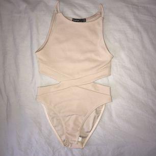 Beige bodysuit från Boohoo, jättefin med cut out på sidan. Aldrig använd!