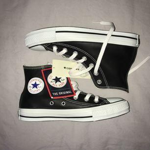 Svarta Converse i läderimitation, storlek 36 men kan passa en 37. Orginalkartong medföljer. Helt nya!
