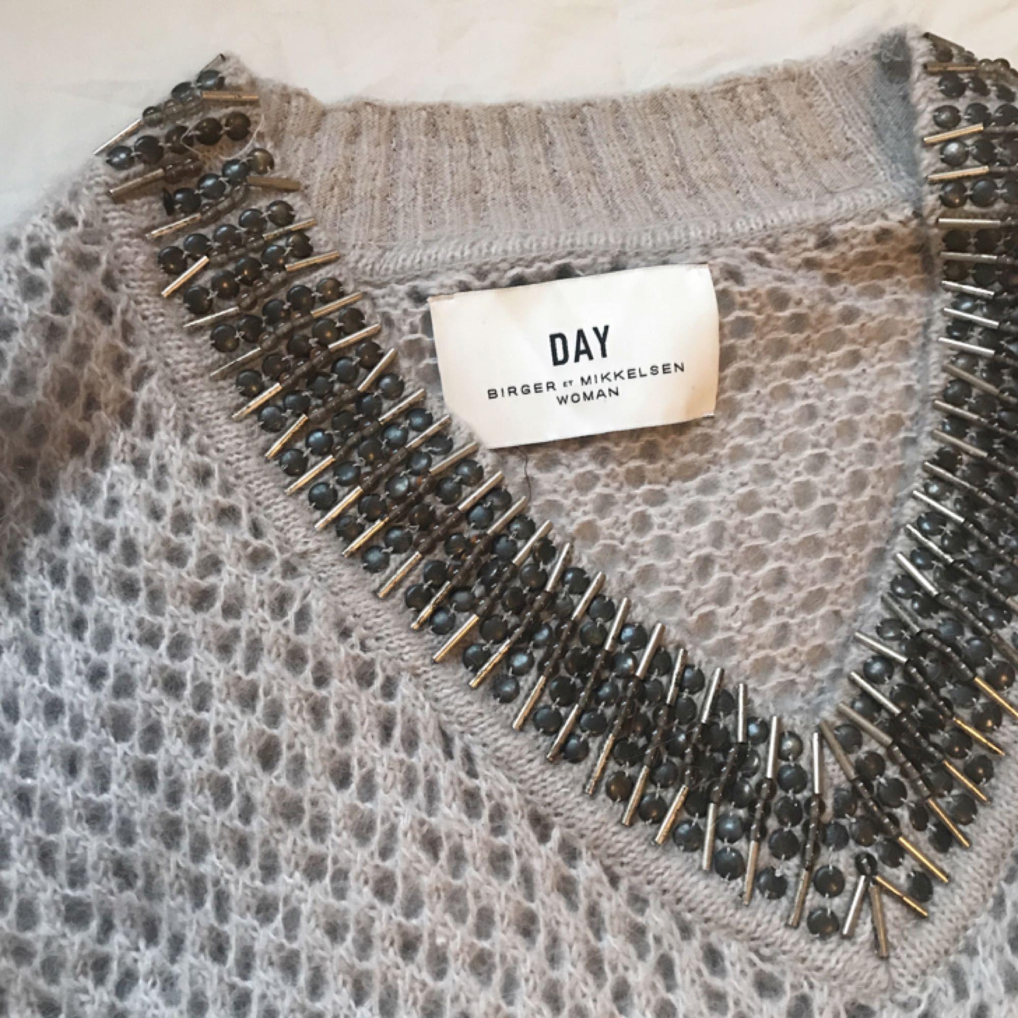 Fin stickad tröja från Day Birger et Mikkelsen. Inte noppig, men någon av stenarna har lossnat. Syns dock inte, den ser i princip ny ut. Kan bäras av S-L beroende på hur man vill att den ska sitta.   Frakt ingår i priset!. Stickat.