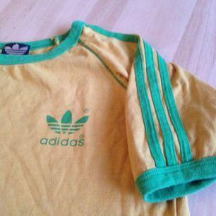 gammal Adidas tröja i senapsgul (blixt på sista bilden det är därför den ser annorlunda ut i färgen!!!) vet ej storlek men skulle säga L dock liten i ärmarna.