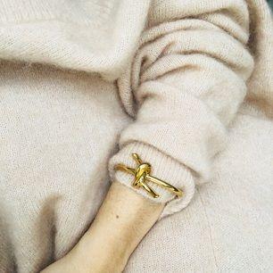 Armband med knut i något slags stål/guldpläterat material. Tål därför fukt utan att bli svart eller fult på en gång. Riktigt tungt och välgjort.   FRI FRAKT.