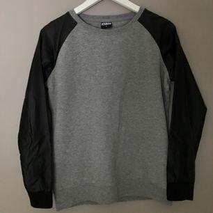 Sweatshirt från Urban Classics som tyvärr aldrig kommer till användning. Grå med ärmar i fejk-skinn. Som ny ✨ Köparen står för eventuell frakt!