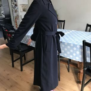 Owow it's a trench coat long. I'm a 1.68 and this coat falls right above my ankle. It's super new, rarely worn. Marine blue. I had a marine blue period and now I'm falling out of it.