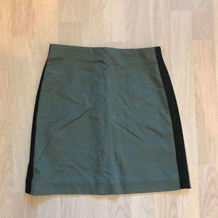 Grön kjol med svarta revärer, använd en gång.
