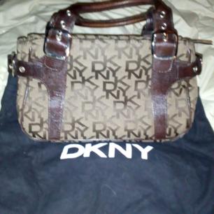 DKNY väska, brun skinn o tyg, lite använd, kommer med dustbag. Den är äkta!!!