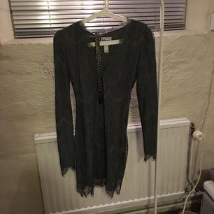 Supersnygg grå spetsklänning från Rebecca Stella x Nelly. Det hör även till ett snyggt midjeskärp. Klänningen är en mjuk och skön fodralklänning med lagom urringning.   Frakt tillkommer och betalning sker via swish.