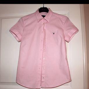 Helt oanvänd skjorta/blus från Gant i en ljus rosa färg. Oxfordskjorta i stretchig egyptisk bomull. Bomull 97%, elastan 3%. Den här figursydda modellen har enkel krage, korta ärmar, hälla bak och en klassisk broderad GANT-sköld på bröstet. Inköpt på Gant butiken på Birger Jarlsgatan i Stockholm för 899 kr.   MÖTS ENDAST UPP I STOCKHOLM!