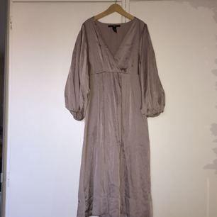 """Fin klänning i silkestyg från H&M med halvlång """"puffärm"""". Strl 34. Färgen är ljust gammelrosa"""