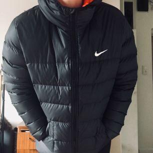 Snygg Nikejacka i nyskick, orange foder och svart utsida, snygg luva, värmer bra under vintern. Funkar även till snowboard åkning.