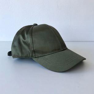 Keps i militärgrönt från H&M. Går att spänna baktill. Sparsamt använd. Köparen står för frakt.
