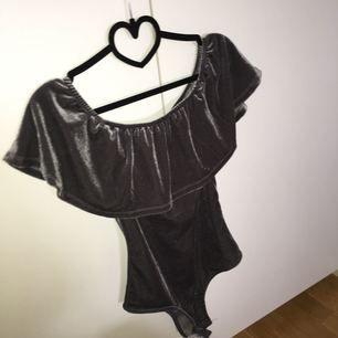 En fin bodysuit i grå sammet med volang. Den är tyvärr för liten för mig:(