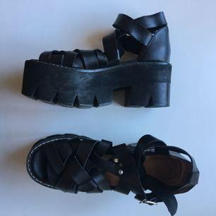 Storlek 38, Jeffrey Campbell platå sandal i läder.  De är använda få gånger. Då de var för stora för mig, jag har 37,5. Tyvärr är de lite klibbiga i hälen, för jag försökte sätta dit hälgrepp, som jag nu tagit bort.  Köpare betalar frakt/Meet up i Sthlm