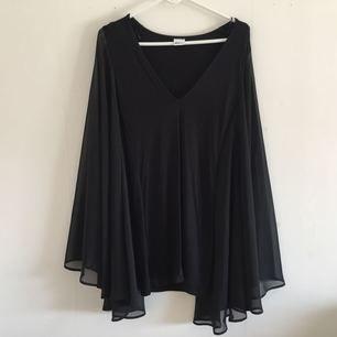 Svart klänning med stora chiffongärmar. Skickas fraktfritt på posten.