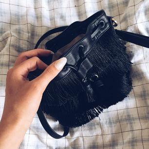 """Svart väska från Zara i """"pås"""" form ungefär, man kan dra åt längst upp. Har fransar. Frakt tillkommer om varan behöver skickas"""