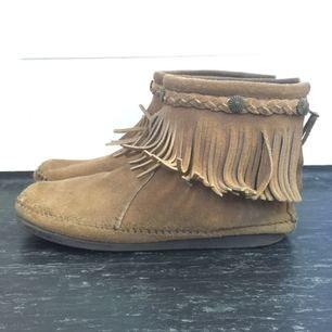 minnetonka skor i ljusbrun mocka, storlek 39. Jag som har 38 kan ha dom med en sula i.  Använda en säsong. Fransarna hänger ut sig efter ett tag.