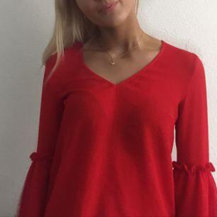 Röd fin blus i bra skick med volanger på ärmarna och  fin öppen rygg med rosett
