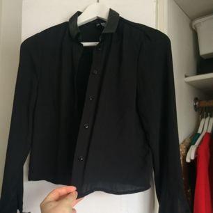 Skjorta med skinndetaljer på kragen och ärmslutet skirt material