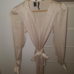 Omlott blus i silke från Mango Krämvit Midjeskärp Liten knapp på insidan Diamantknappar i ärmarna