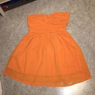 Orange klänning med vadderade kupor och med synlig dragkedja bak