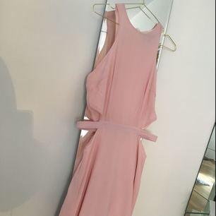 En ljusrosa fin långklänning. Slits framtill. Använd en gång på ett bröllop. Storlek 10 vilket jag tror motsvarar 36.